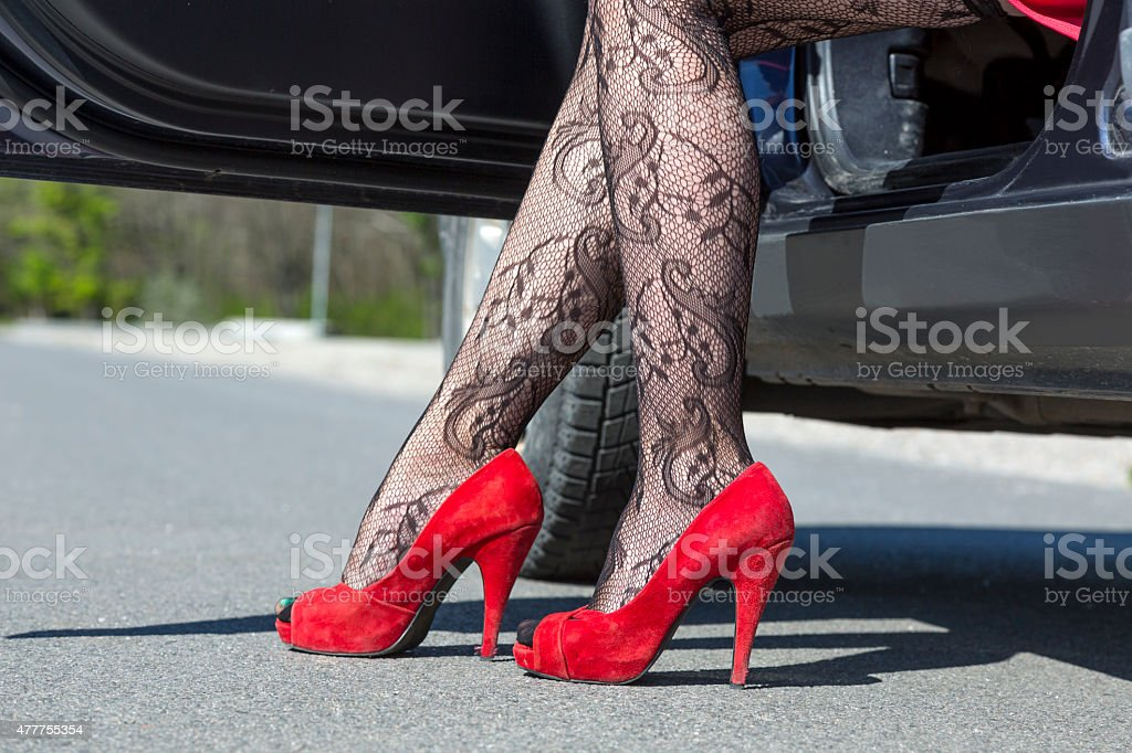 Feet of stylish female driver walking out of car stock photo