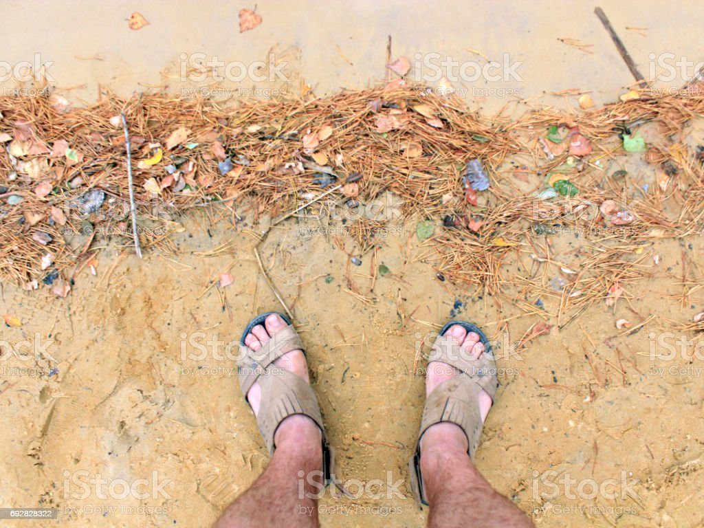 feet of the traveller standing on the sand stock photo