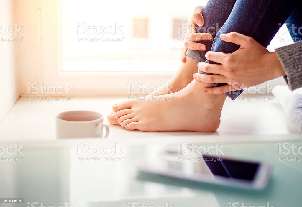 Feet of unrecognizable woman sitting on window sill stock photo