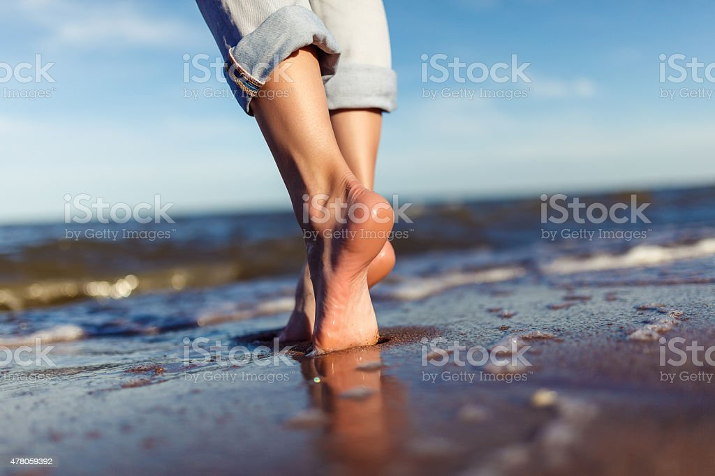 feet of woman  in the sea waves stock photo