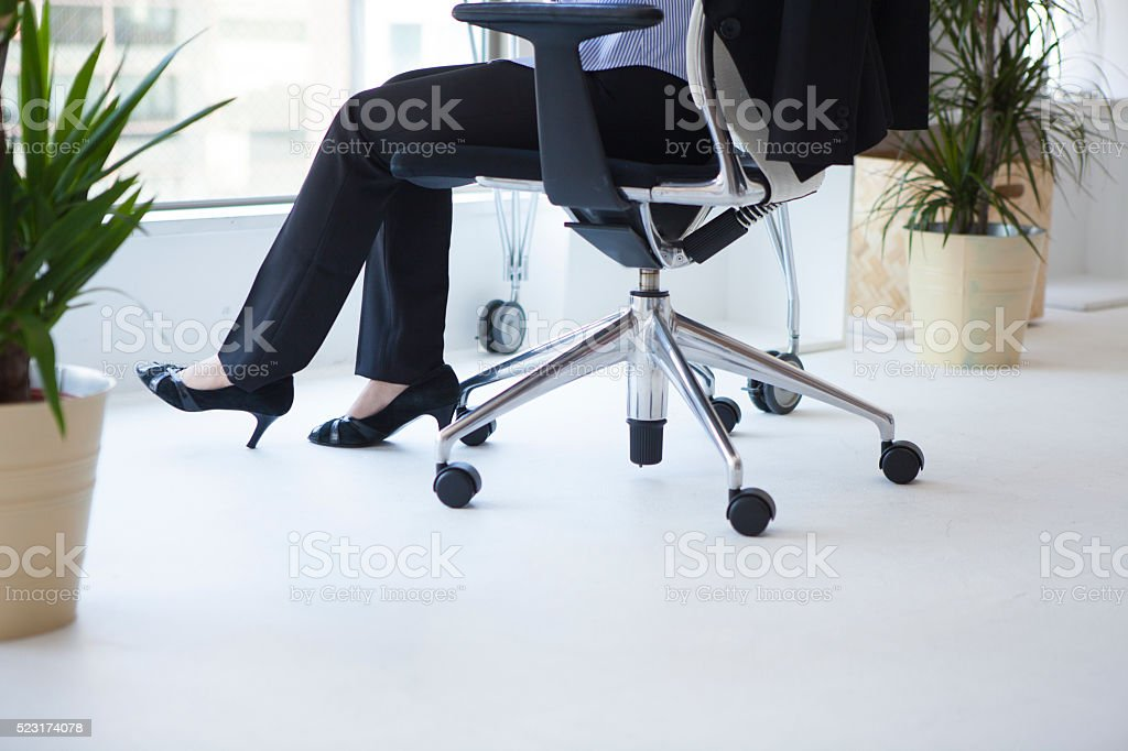Feet of woman wearing high heels sitting in your chair stock photo