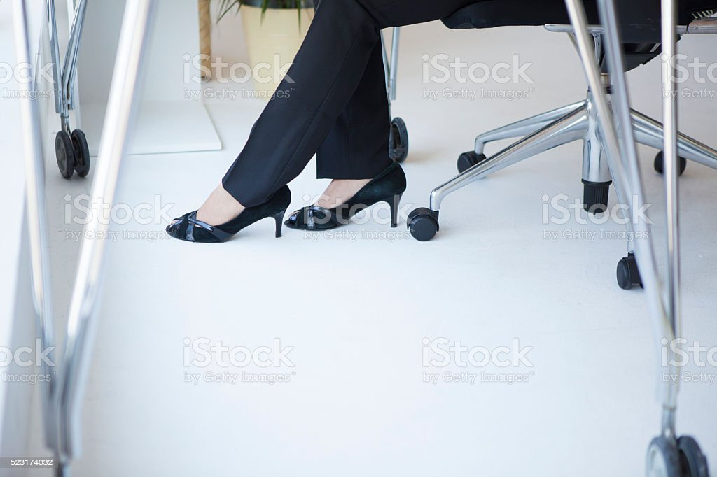 Feet of woman wearing high heels to work in office stock photo