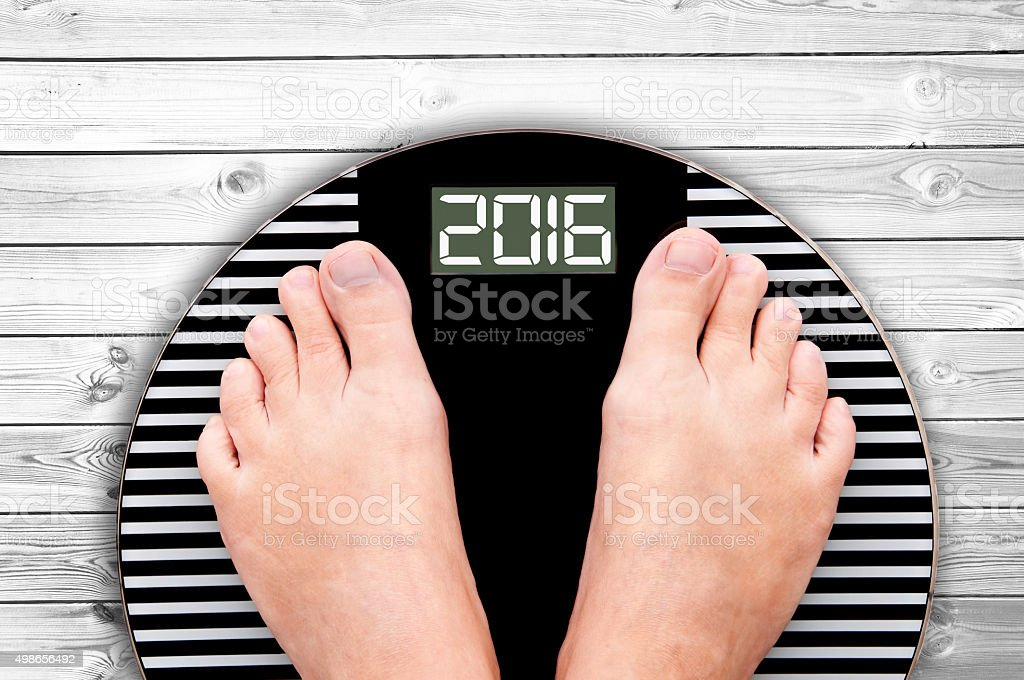2016 feet on a weight scale on wooden floor background stock photo