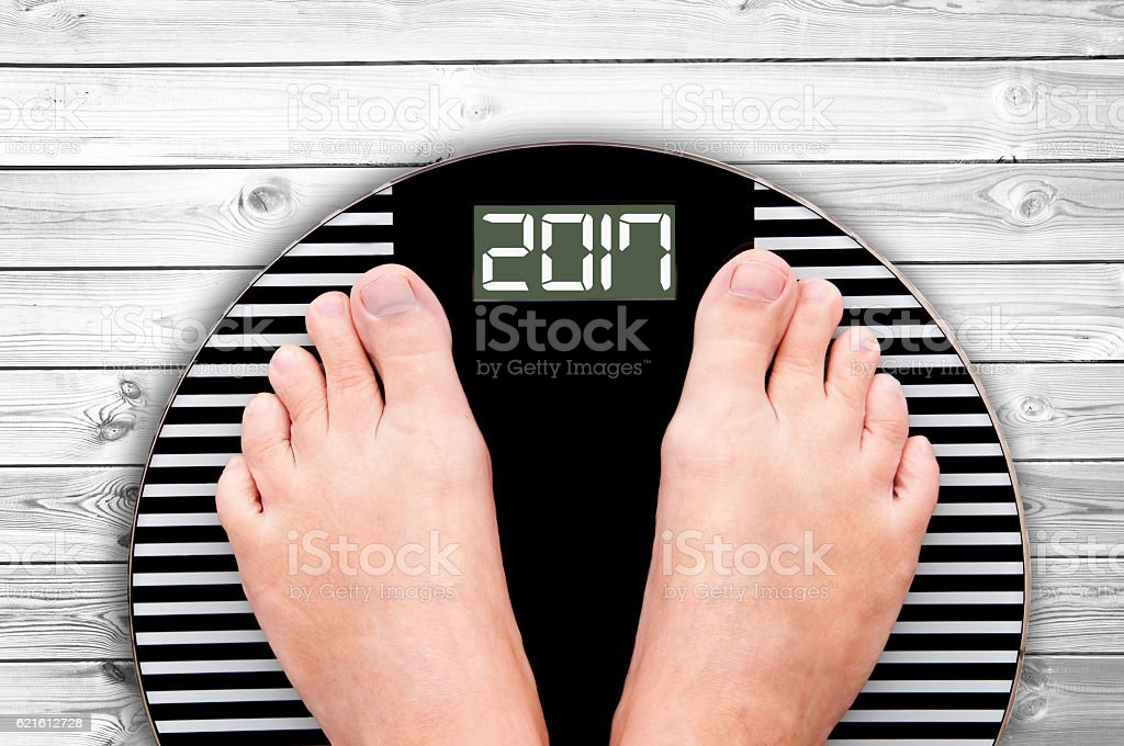 2017 feet on a weight scale, white wooden floor background stock photo