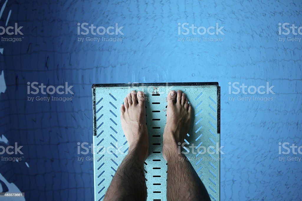 feet on diving board over pool stock photo