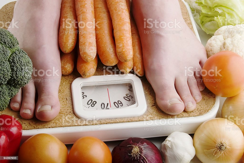 Feet on scale surrounded by fresh, healthy vegetables royalty-free stock photo