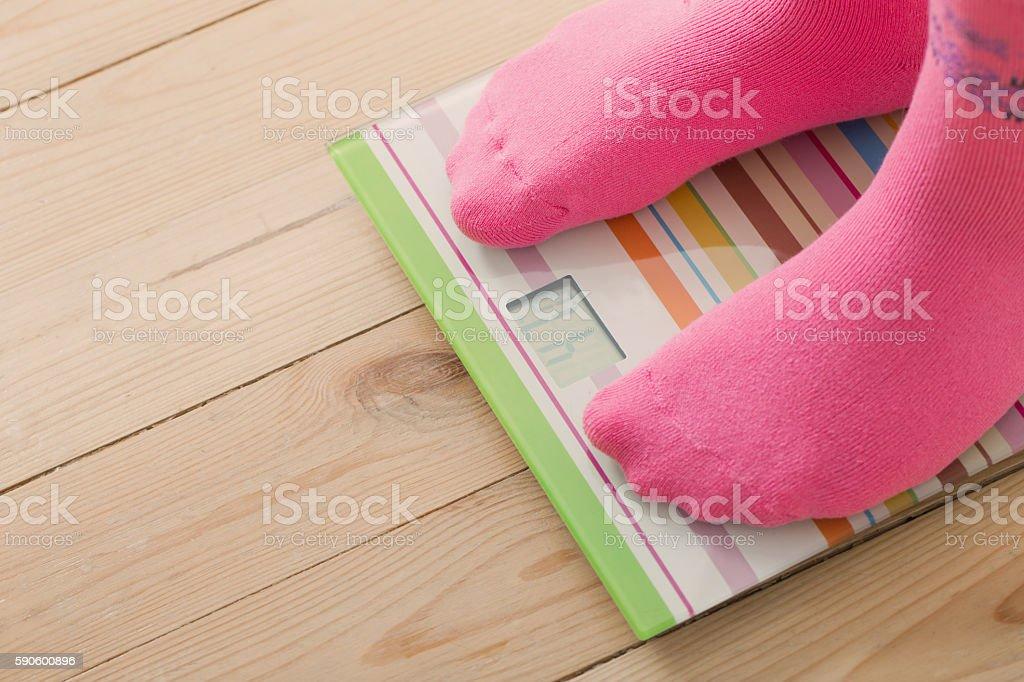 Feet on scales on wooden floor stock photo