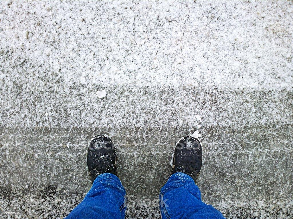 Feet on the asphalt in the snow. stock photo