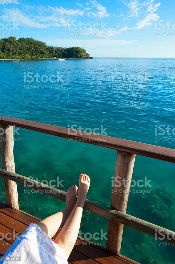 Feet on the balcony of over water bungalow stock photo