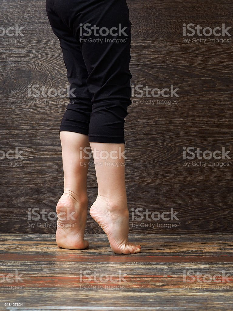 Feet on the floor of the child standing on tiptoe stock photo
