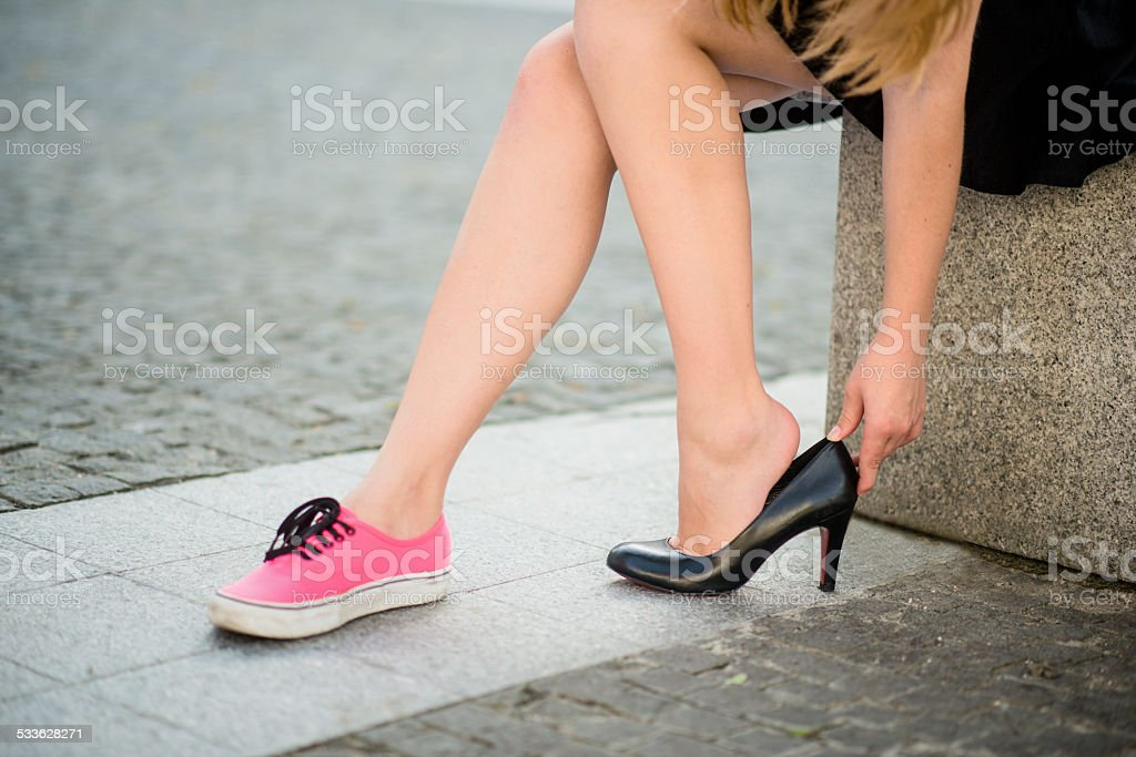 Feet pain - changing shoes stock photo