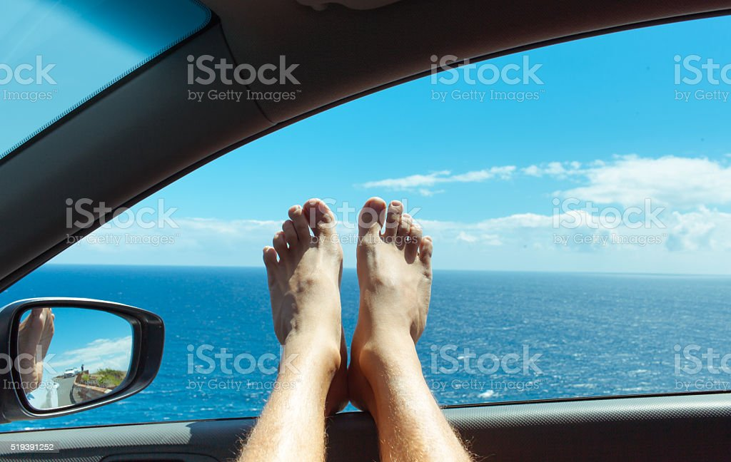 Feet relaxing in a car by the sea stock photo