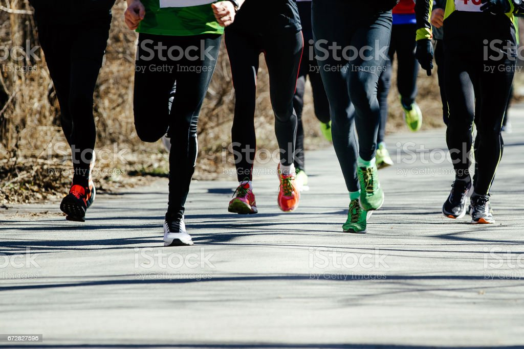 feet runners group leaders runnnig on asphalt road in a city park