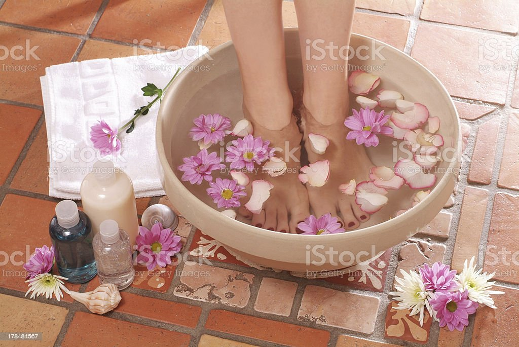 Feet stood in bowl of water with flowers next to lotions stock photo