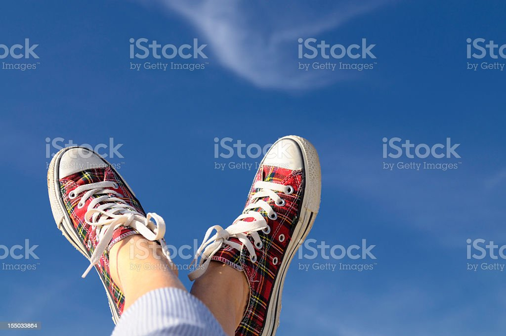 Feet Up W Sport Shoes Against Blue Sky.Copy Space stock photo