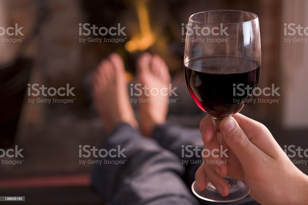 Feet warming at fireplace with hand holding wine stock photo