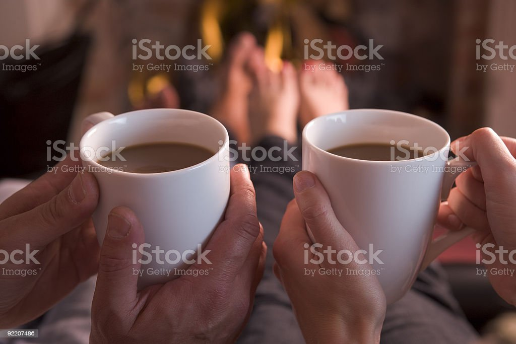 Feet warming at fireplace with hands holding coffee stock photo
