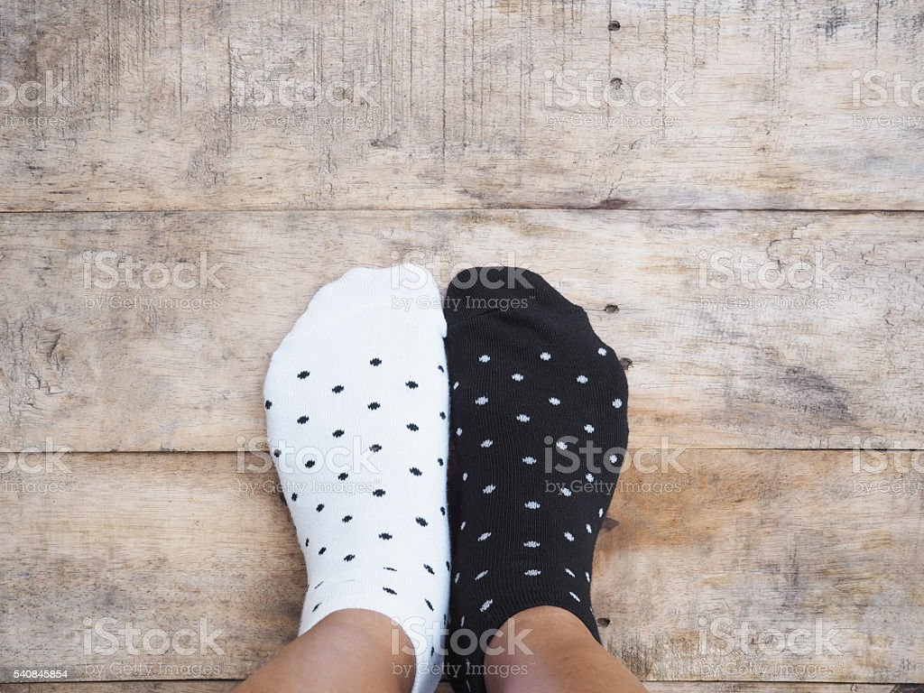 feet wearing black and white polka dot socks stock photo