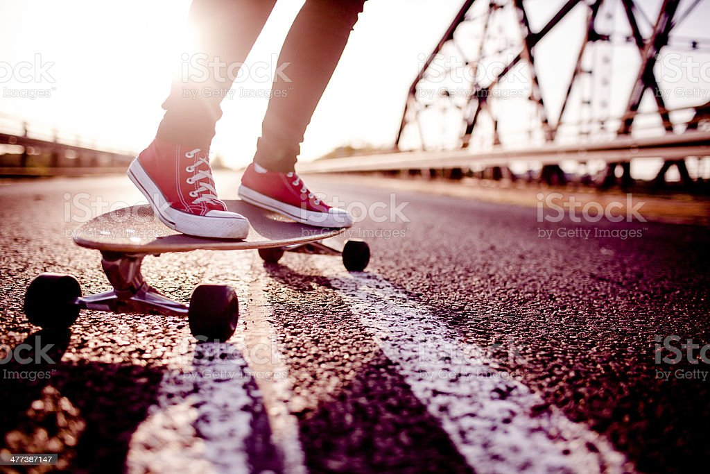 Feet wearing red shoes and riding a long board stock photo