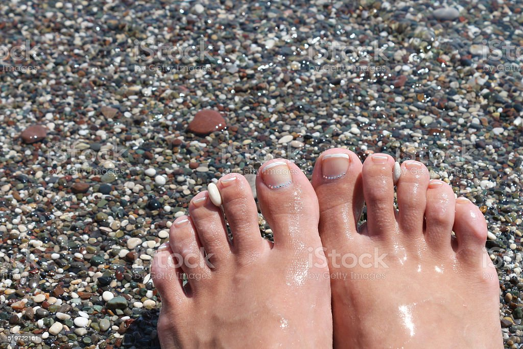 feet with pedicure on the beach stock photo