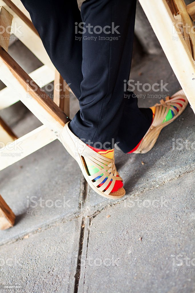 Feet with sandals and multi colored socks stock photo