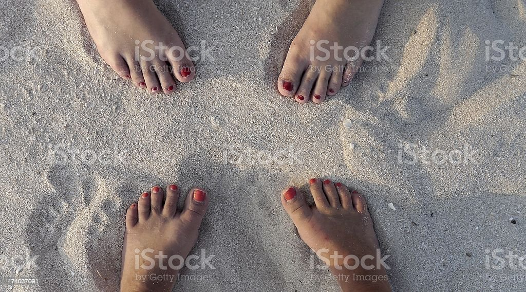 feets in the sand of the beach and ocean sunset stock photo