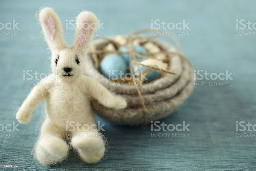 Felt Easter bunny with bowl of eggs in background royalty-free stock photo