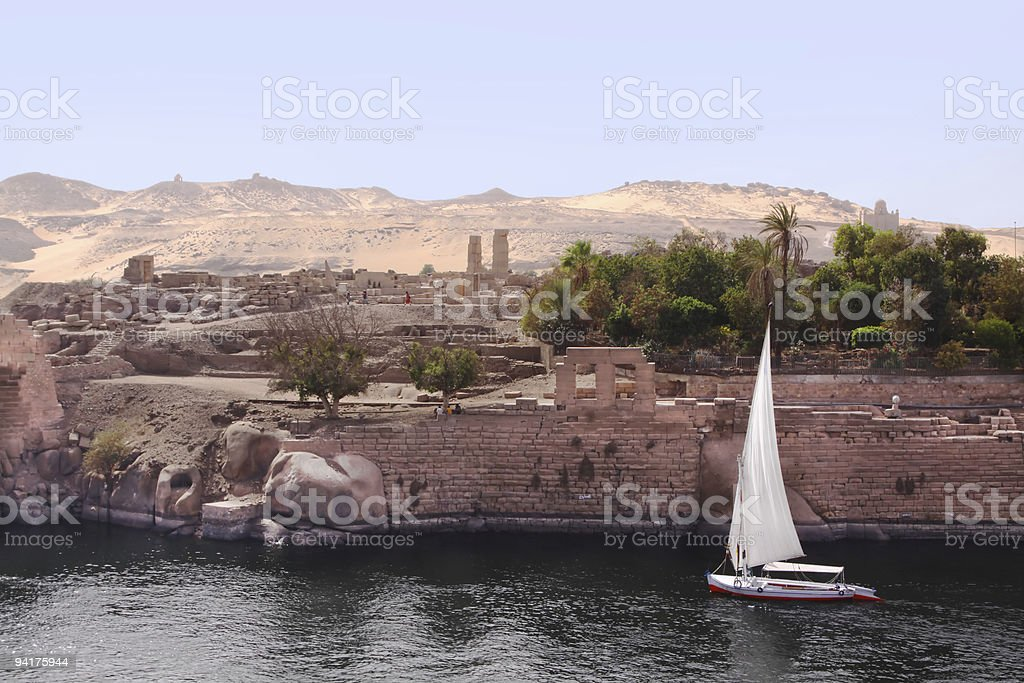 Feluca floats down the nile ruins in background royalty-free stock photo