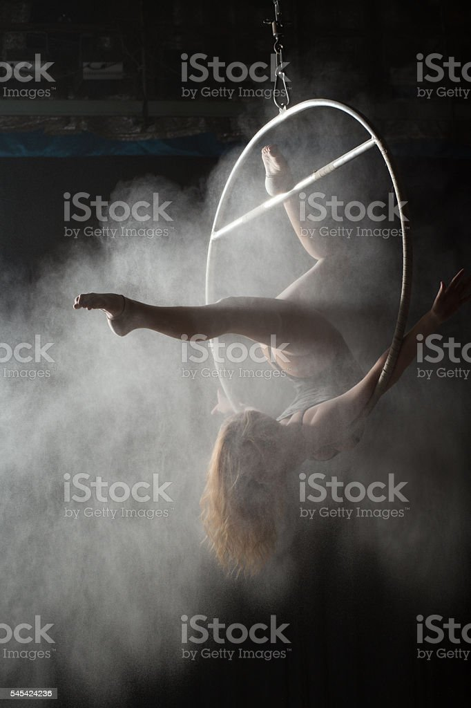 Female acrobat doing gymnastic element on aerial hoop with sprinkled stock photo