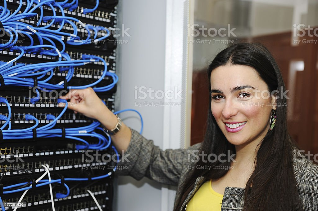 Female administrator at datacenter server room stock photo