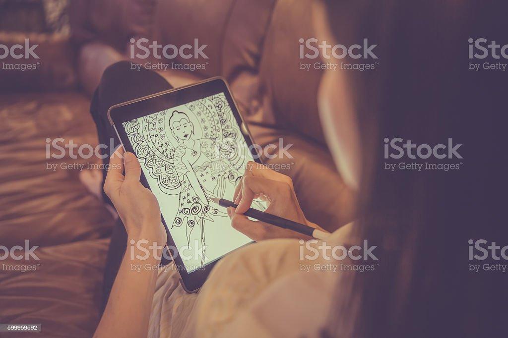 Female Adult Drawing Mandala on Electronic Tablet stock photo