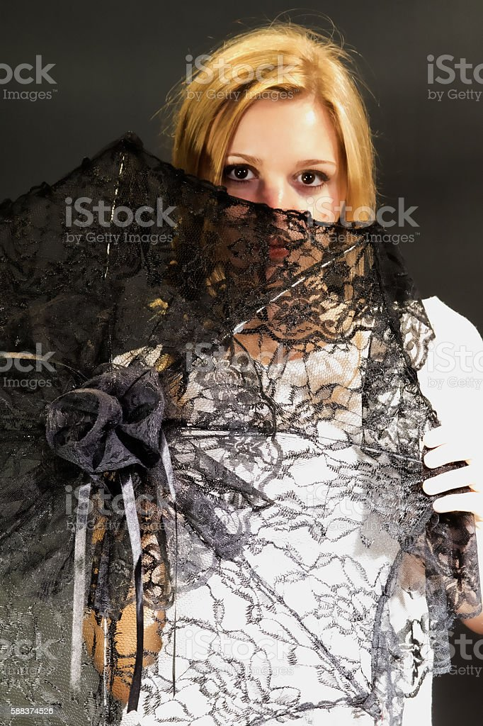 Female Adult Looking Through A Lace Parasol stock photo