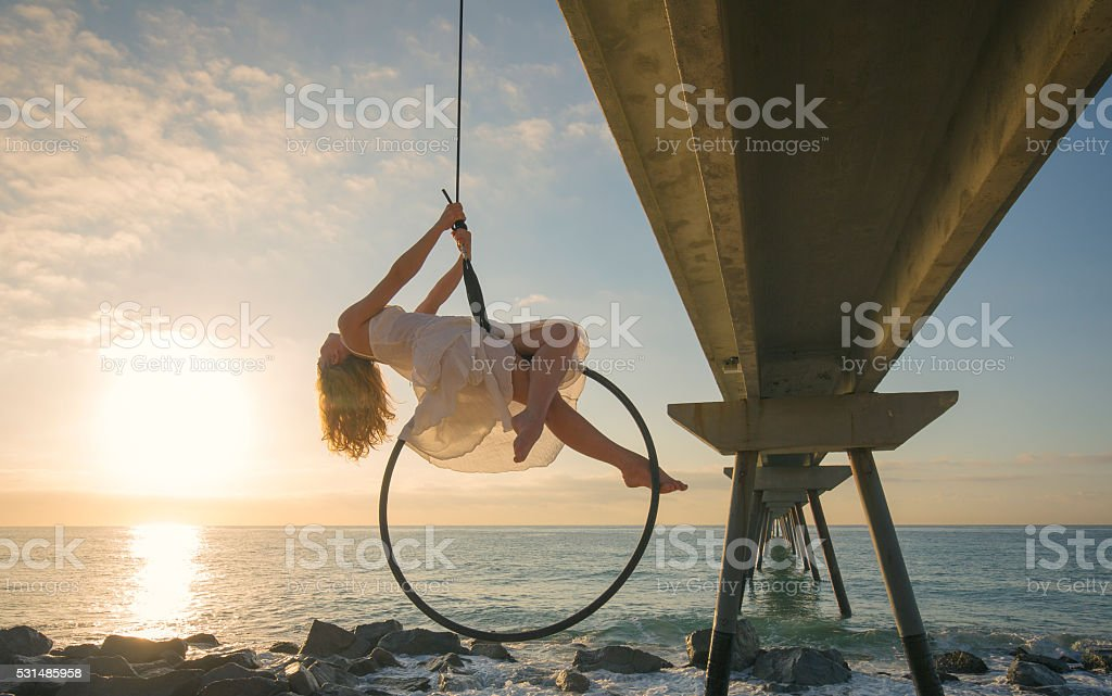 Female aerial dancer at sunrise over the sea stock photo