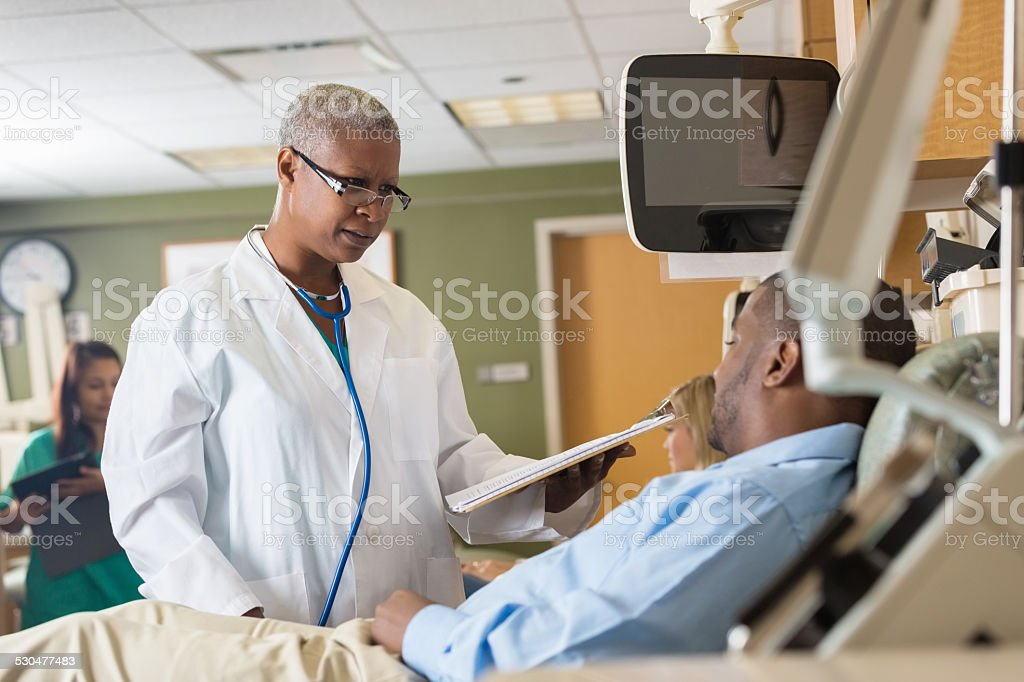 Female African American doctor explaining chart to patient in hospital stock photo