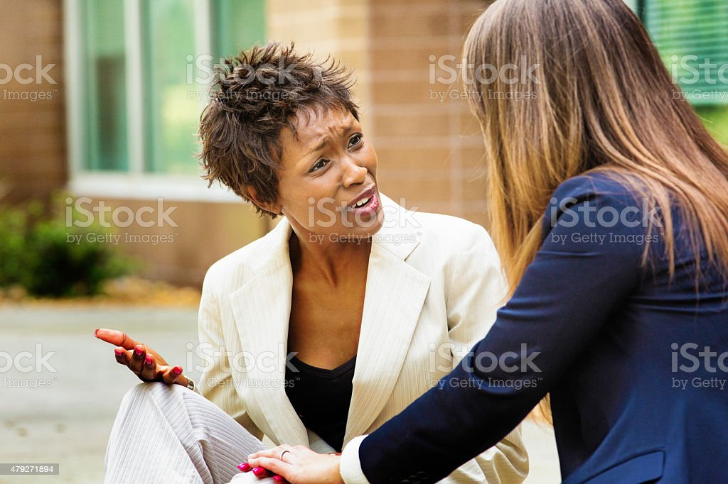 Female African American office worker reacts negatively to bad news stock photo