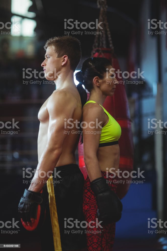 Female and male boxer standing back to back stock photo