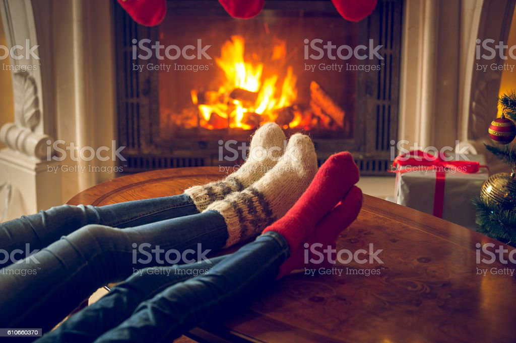 Female and male feet in wool socks warming at fireplace stock photo