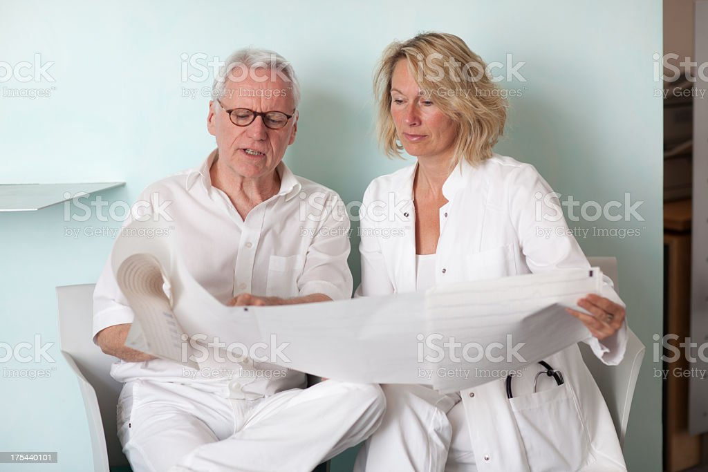 female and male mature doctors talking about an eeg stock photo