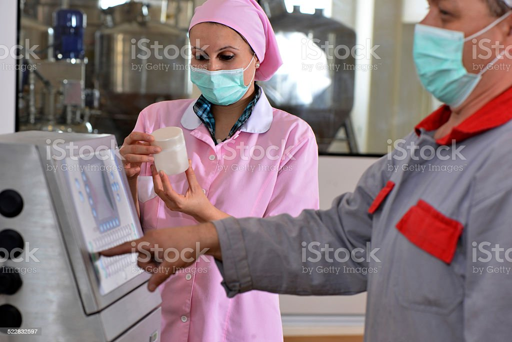 Female and male worker examining new beauty product stock photo