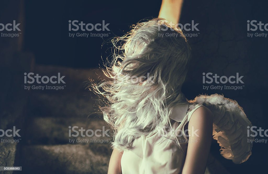 Female angel in white with obscured face. stock photo