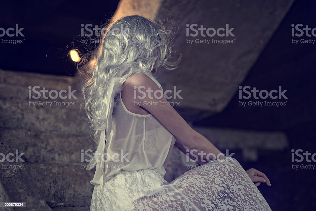 Female angel with obscured face on staircase. stock photo