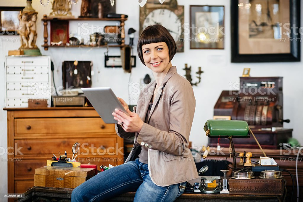 Female antique store owner using digital tablet stock photo