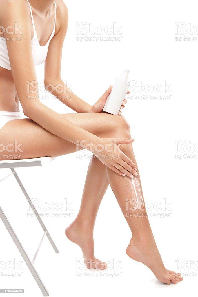 Female applying cream on legs stock photo
