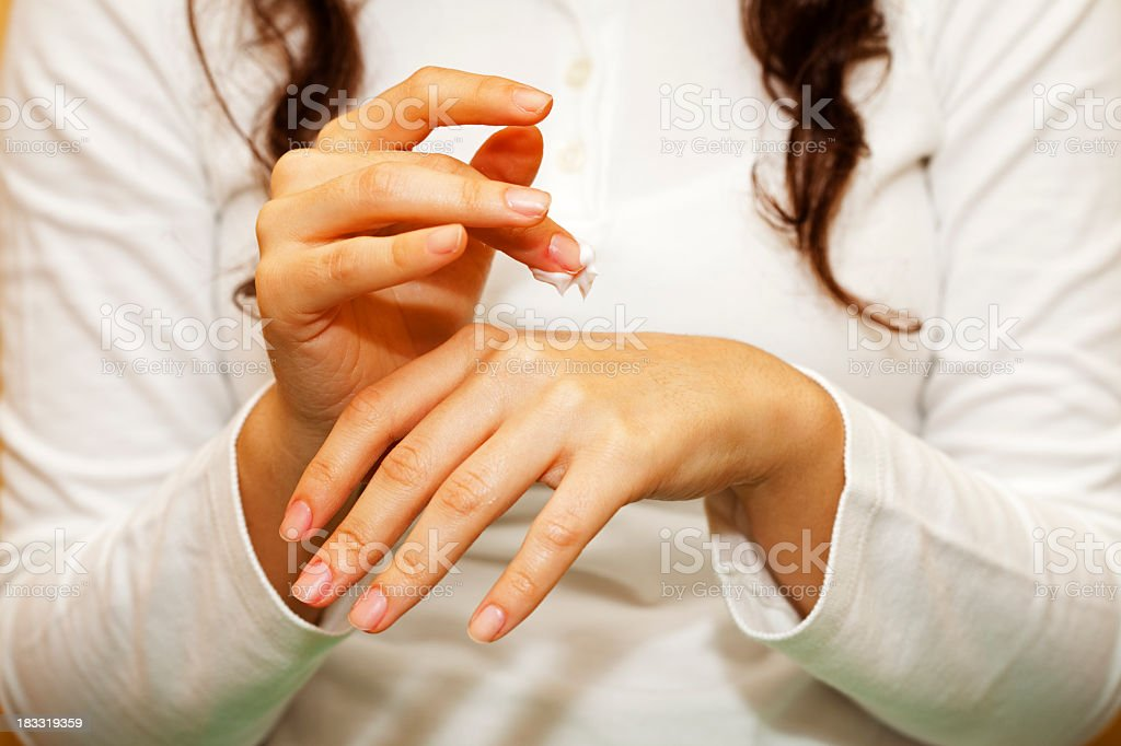 Female applying hand cream on her left hand stock photo