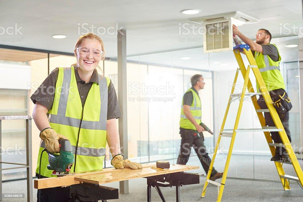 female apprentice carpenter on site stock photo