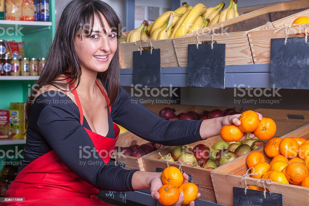 female arabian shop assistant at the greengrocer stock photo