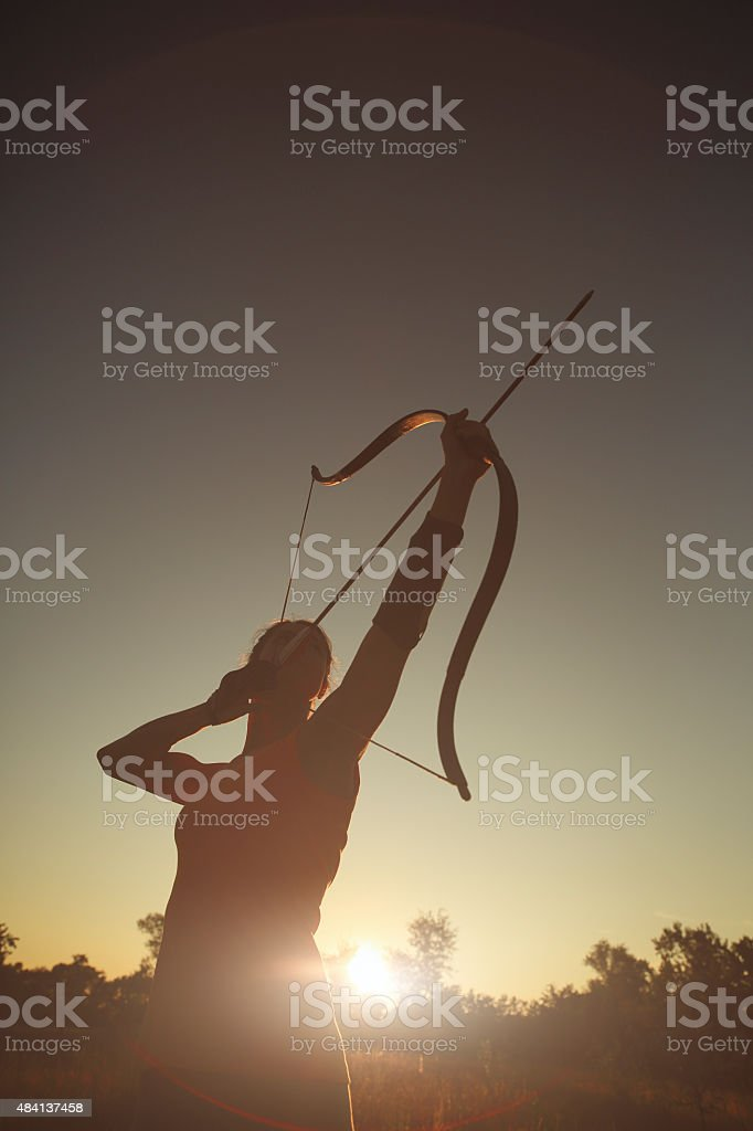 Female archer in the field at sunset stock photo