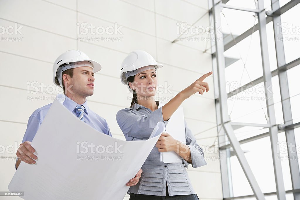 Female architect pointing at something to a male colleague royalty-free stock photo