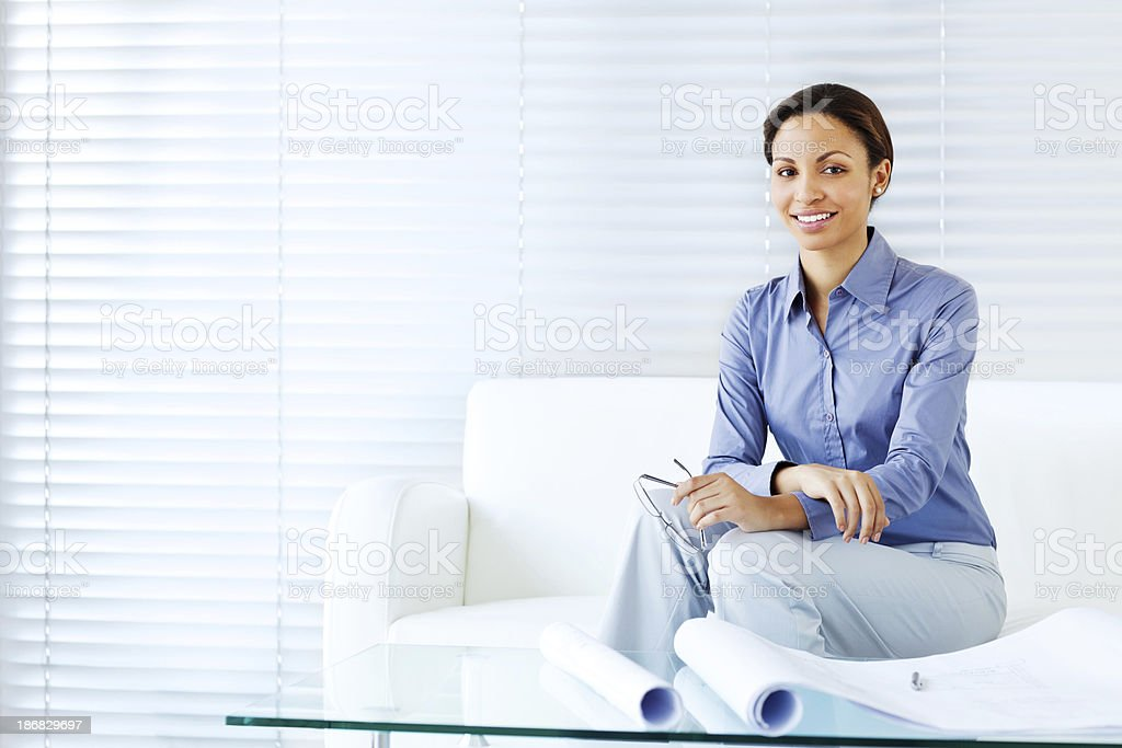 Female Architect Sitting on Sofa with Blueprints royalty-free stock photo