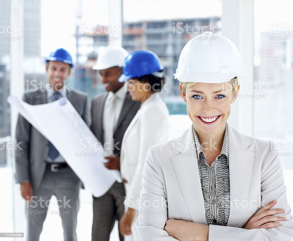 Female architect smiling with colleagues planning in the background royalty-free stock photo